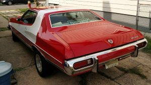 A classic Ford Torino painted red with a white stripe like in Starsky and Hutch.