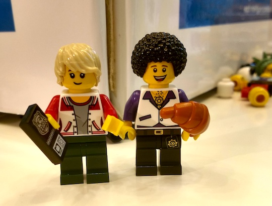 Two LEGO men, one blond in a red letter jacket holding a police badge, and one with dark curly hair in an open-collared disco shirt holding a croissant.